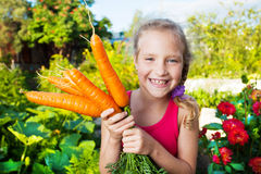 Happy girl with carrot. Child with carrot. Girl with vegetables in garden stock photo
