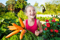 Happy girl with carrot Stock Photos