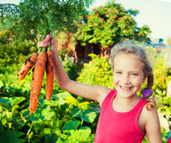 Happy girl with carrot Royalty Free Stock Photos