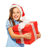 Happy girl carry Christmas present in Santa hat Royalty Free Stock Images
