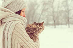 Happy girl with a cat. Young happy woman holds a cat in winter weather, concept of friendship Royalty Free Stock Photos