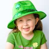 Happy girl celebrates St. Patrick's Day. Closeup of a smiling little girl with brunette hair dressed in green and wearing a fancy green hat to celebrate St Stock Photography