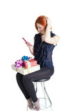 Happy girl on a chair with a telephone and a gift box Stock Image