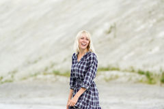 The happy girl in a checkered dress outdoors. Stock Photography