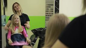Happy girl checking her new haircut in salon stock video