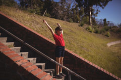 Happy girl cheering on staircase during obstacle course. In boot camp stock photos