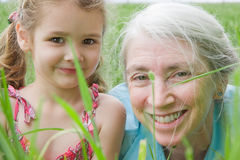 Happy girl child and grandmother in field. Closeup girl and her grandmother in long grass Stock Photography