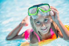 Happy girl child playing in the pool on a sunny day. Cute little girl enjoying holiday vacation Stock Photo
