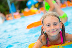 Happy girl child playing in the pool on a sunny day. Cute little girl enjoying holiday vacation Stock Images