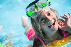 Happy girl child playing in the pool on a sunny day. Cute little girl enjoying holiday vacation Royalty Free Stock Photos