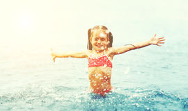 Happy girl child plays and swims with splashes on the beach Royalty Free Stock Image