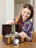 Happy girl chooses jewelry in treasure chest Royalty Free Stock Image