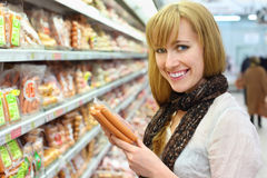 Happy girl chooses sausage in store royalty free stock photo