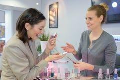Happy girl choosing between bottles nail polish stock image