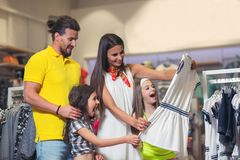 Happy girl choosing clothes. Family are shopping in a children`s store Royalty Free Stock Images