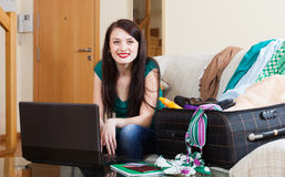 Happy girl choosing the resort on the internet. Using laptop at home Stock Images