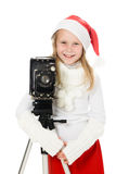 Happy girl in a Christmas costume with old camera Royalty Free Stock Photography