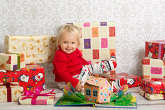 Happy girl among the christmas presents. Dressed festively girl with stacks of present boxes around sitting on the floor and smiling Royalty Free Stock Image