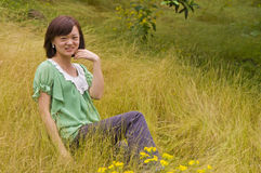 Happy girl in citrus orchard. A graceful chinese girl was sitting in the citrus orchard which with full of yellow weeds stock images