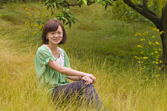 Happy girl in citrus orchard. A graceful chinese girl was sitting in the citrus orchard which with full of yellow weeds stock image