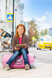 Happy girl with city map sit alone on pink luggage Stock Photography