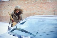 Happy girl cleaning her car from the snow in the city. By the house broom Royalty Free Stock Image