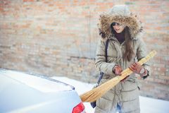 Happy girl cleaning her car from the snow in the city. By the house broom Stock Photos