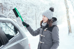 Happy girl cleaning her car of snow in the winter Royalty Free Stock Photography