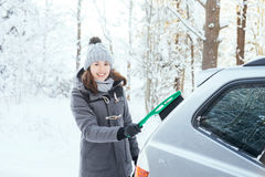 Happy girl cleaning her car of snow in the winter Royalty Free Stock Photo
