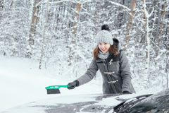 Happy girl cleaning her car of snow in the winter Stock Photo