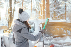 Happy girl cleaning her car of snow in the winter Stock Image