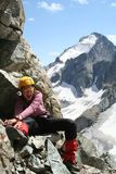 Happy girl climber. Sitting on a rock and smiling Stock Images