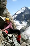 Happy girl climber. Sitting on a rock and smiling Stock Image
