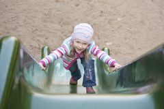 Happy girl  climbing on children's slide Royalty Free Stock Photo