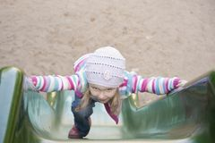 Happy girl  climbing on children's slide Royalty Free Stock Images