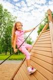 Happy girl climbs on wooden construction Stock Photos