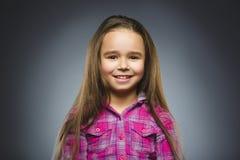 Happy girl. Closeup Portrait handsome child smiling on grey stock photo