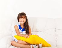 Happy girl on the coach with pillow Stock Image
