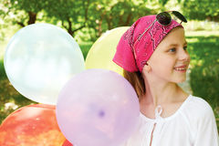 Happy girl  with colorful balloons. Happy girl is in a amusement park with colorful balloons Royalty Free Stock Photography