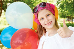 Happy girl  with colorful balloons. Happy girl is in a amusement park with colorful balloons Stock Photo