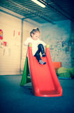 Happy girl on colorful slide Royalty Free Stock Photography