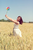 Happy girl with a colorful windmill Stock Images