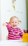 Happy girl with coloring pencils. Happy toddler girl with coloring pencils Royalty Free Stock Images