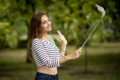 Happy girl communicate with friends over the internet and greets by waving his hand in a city park with smartphone on selfie stick stock photography