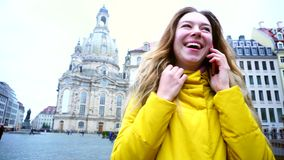 Happy girl communicating on mobile sharing emotions and smiling broadly, in middle of center of beautiful European city stock video