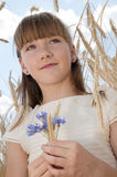 Happy girl in communion dress. Portrait of happy young girl in communion dress surrounded by field of barley; blue sky and cloudscape background Stock Photos