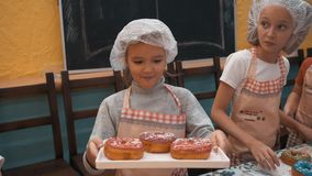 Happy girl in cook hat and apron showing tray with glazed donuts on culinary master class. Cute cook girl with baked stock video footage