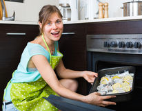 Happy girl cooking fish in oven Stock Photo