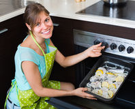 Happy girl cooking fish in oven Royalty Free Stock Photography