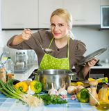 Happy girl cooking at  kitchen. Portrait of happy girl cooking with vegetables at  kitchen Royalty Free Stock Photography